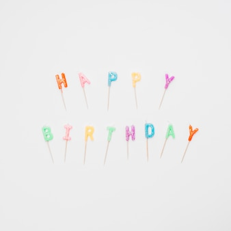 Feliz aniversário colorido rotulando velas no fundo branco