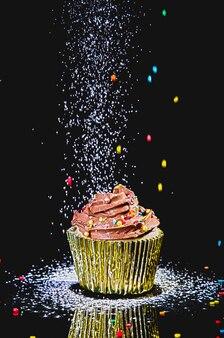 Feliz aniversário com cupcake de chocolate em fundo preto