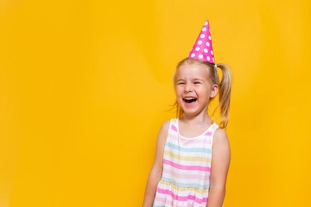 Feliz aniversário criança menina com dois ponytales na tampa rosa rindo sobre fundo amarelo colorido. espaço para mensagem.