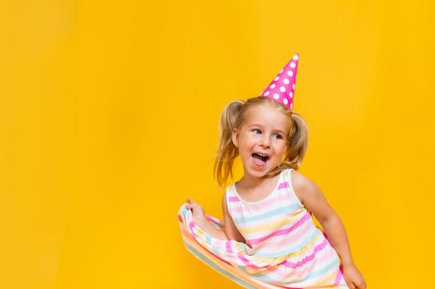 Feliz aniversário criança menina com dois ponytales na tampa rosa sobre fundo amarelo colorido, shoing a língua.