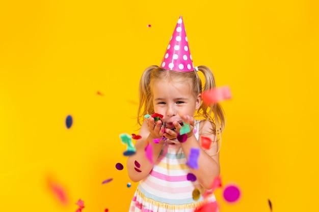 Feliz aniversário criança menina em copo rosa soprando confetes na parede amarela colorida. celebração, infância.