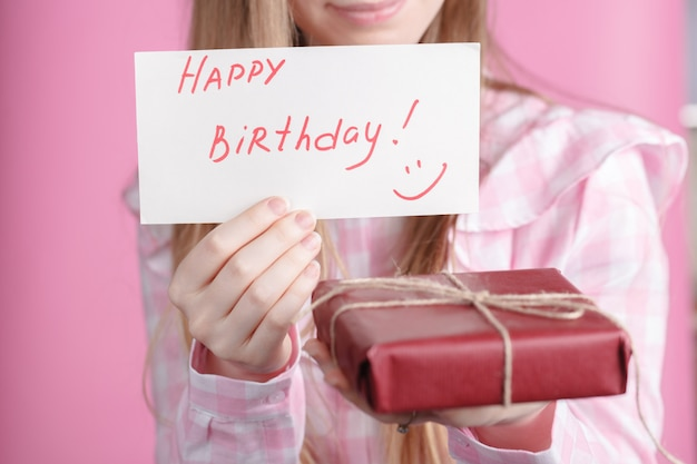 Feliz aniversário de palavras e caixa de presente em mãos femininas