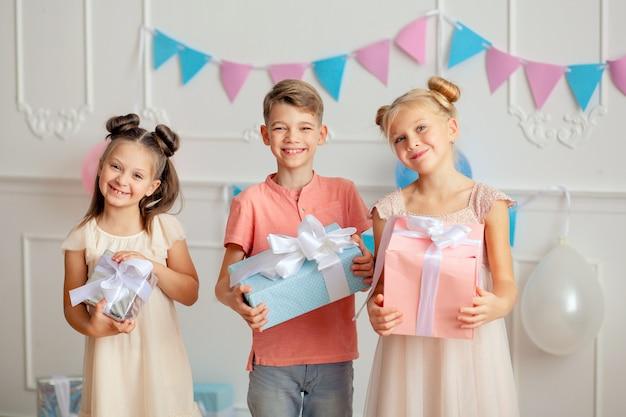 Feliz aniversário felizes filhos bonitos em uma decoração festiva e lindos vestidos com presentes nas mãos.