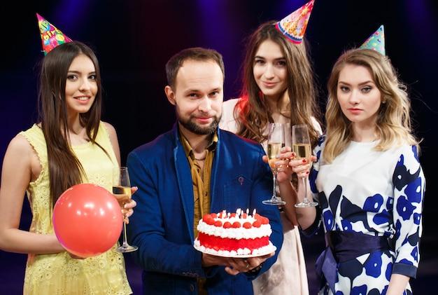 Feliz aniversário! grupo de amigos sorridentes reunidos com bolo.