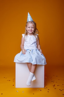 Feliz aniversário menina com confete colorido sobre um fundo amarelo, sentado em um cubo branco