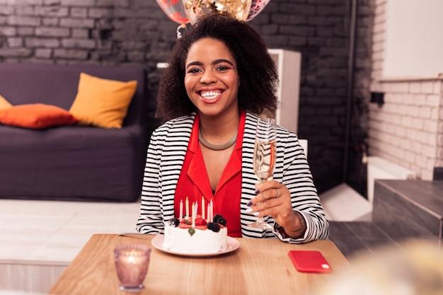 Feliz aniversário. mulher simpática e encantada segurando uma taça de champanhe enquanto comemora seu aniversário