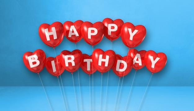 Feliz aniversário vermelho em forma de coração balões de ar em uma cena de superfície azul