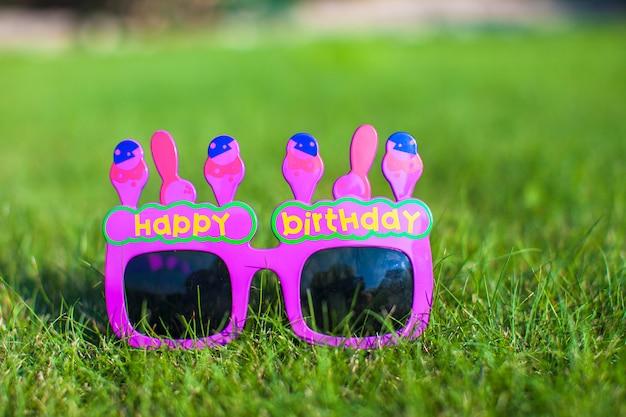 Feliz aniversário vermelho óculos na grama