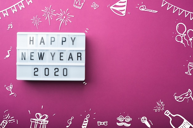 Feliz ano novo 2020 caixa de luz com doodle item decoração férias item vista superior na mesa roxa
