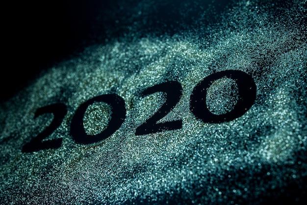 Feliz ano novo 2020. colagem criativa dos números dois e zero, composta pelo ano 2020. lindo espumante dourado número 2020 no preto