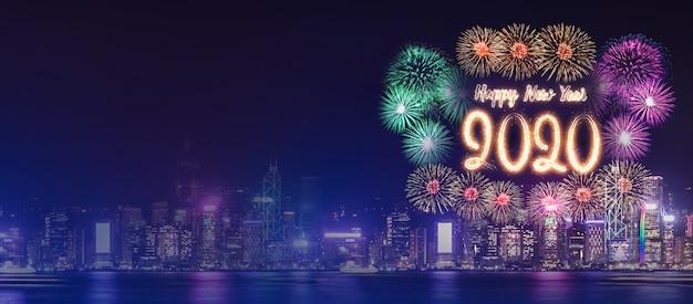 Feliz ano novo 2020 fogo de artifício sobre a paisagem urbana de construção perto do mar em comemoração à noite