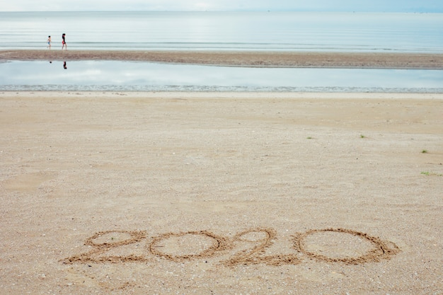 Feliz ano novo 2020, letras na praia com ondas e mar azul claro.
