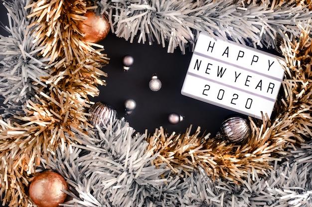 Feliz ano novo 2020 lightbox. vista superior do ouropel, bola, festa de ornamento