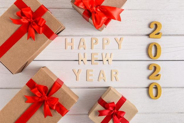 Feliz ano novo 2020 texto em madeira para o ano novo com caixa de presente