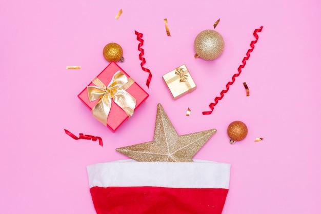 Feliz ano novo 2021. brinquedos de natal, caixas de presente, boné vermelho, sobre um fundo rosa. natal.