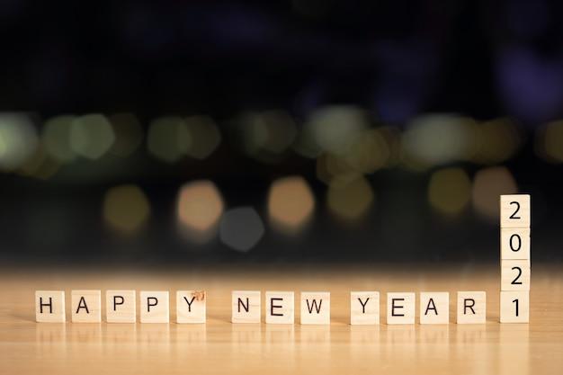 Feliz ano novo 2021 com cubo de madeira na mesa com bokeh de fundo desfocado.