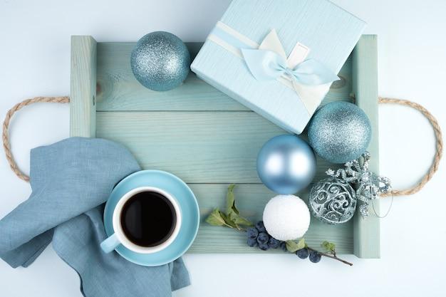 Feliz ano novo 2021, composição festiva com uma xícara de café, caixa de presente, balões de natal e uma bandeja em azul suave
