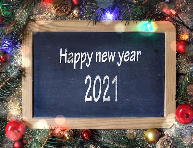 Feliz ano novo 2021 escrevendo em uma lousa no enfeite de natal