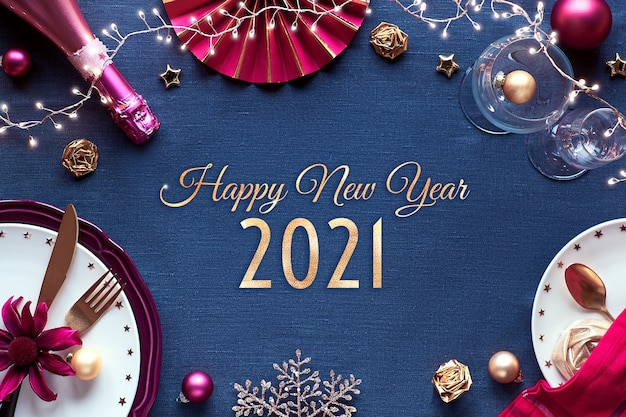 Feliz ano novo 2021 texto dourado no quadro com configuração de mesa de festa de ano novo. decoração dourada, rosa e vermelha em tecido de linho.