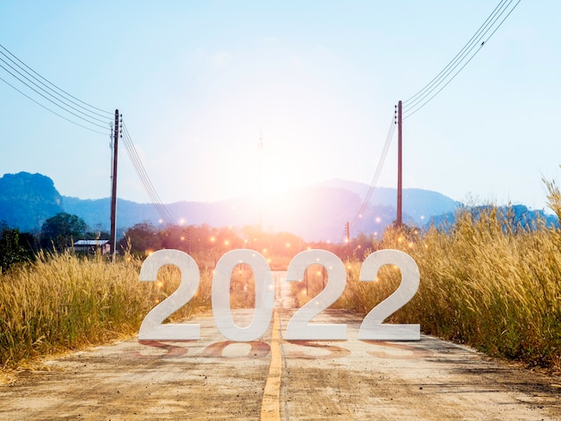 Feliz ano novo 2022 com letras grandes na estrada aberta local para a grande montanha no nascer do sol para superar obstáculos, sucesso, futuro, começar e começar com o conceito de objetivo de negócios.