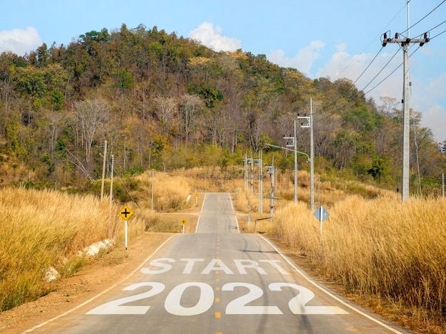 Feliz ano novo 2022 com letras grandes na estrada aberta local para a grande montanha para superar obstáculos, sucesso, futuro, começar e começar com o conceito de objetivo de negócios.