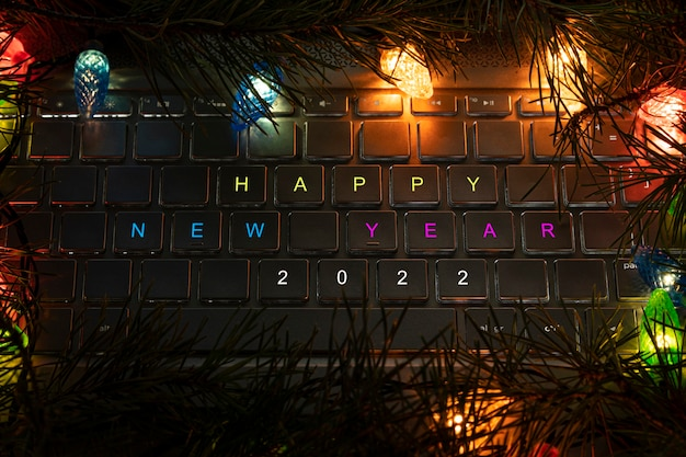 Feliz ano novo 2022 escrito no teclado com luzes de guirlandas no escuro à noite