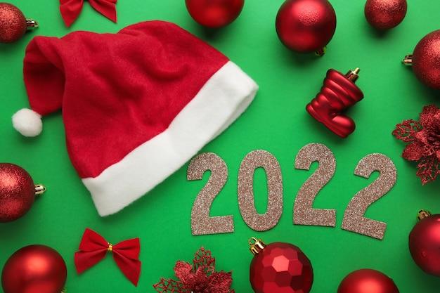 Feliz ano novo 2022. fundo de natal com chapéus de papai noel, bolas de natal e algarismos 2022.