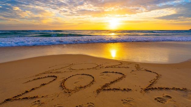 Feliz ano novo 2022, letras na praia com ondas e o céu do pôr do sol números 2022 ano à beira-mar, mensagem escrita à mão na areia dourada no fundo do céu dourado lindo pôr do sol ou nascer do sol.