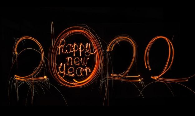 Feliz ano novo 2022 texto em chamas e feliz ano novo 2022 isolado em fundo preto