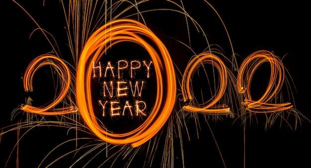 Feliz ano novo 2022 texto queimando e espumante feliz ano novo 2022 isolado em um fundo preto beauti