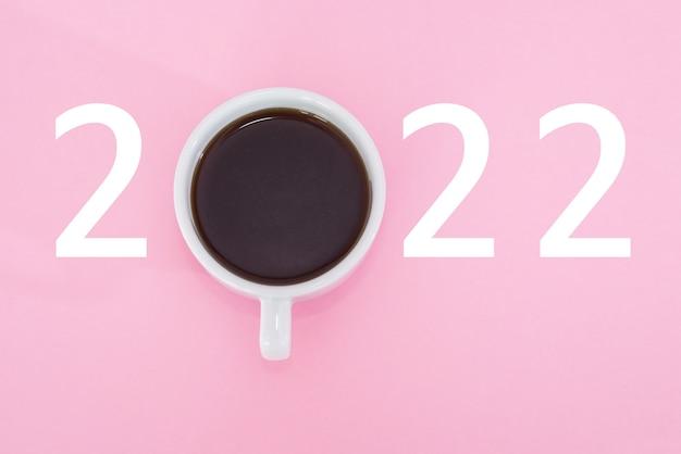 Feliz ano novo 2022. xícara de café com número 2022 em fundo rosa