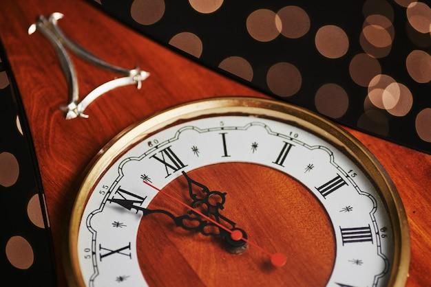 Feliz ano novo à meia-noite, antigo relógio de madeira com luzes do feriado