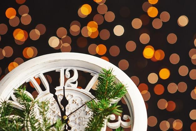 Feliz ano novo à meia-noite, velho relógio de madeira com luzes do feriado e ramos de abeto
