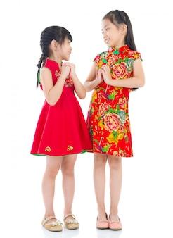 Feliz ano novo chinês! meninas chinesas, em, tradicional, chinês, cheongsam, saudação, para, um ao outro, isolado, branco, fundo