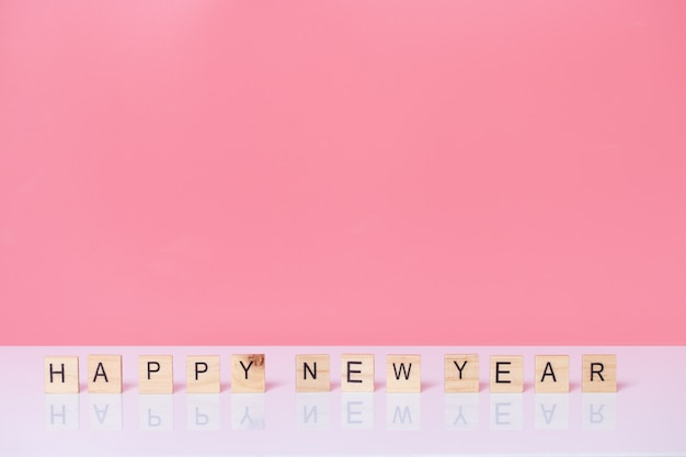 Feliz ano novo com cubo de madeira em fundo rosa.