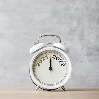 Feliz ano novo com despertador vintage e mudança de 2021 para o número 2022. feliz natal, novo começo, resolução, contagem regressiva, metas, plano, ação e conceito de missão