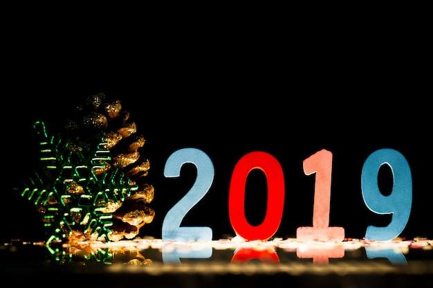 Feliz ano novo de 2019 a figura é feita de madeira na superfície refletiva, espaço da cópia.