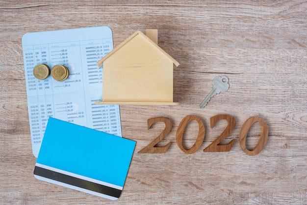 Feliz ano novo de 2020 com banco de livros, modelo de casa e chave