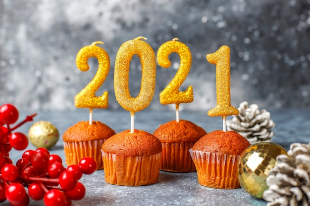 Feliz ano novo de 2021, cupcakes com velas douradas.