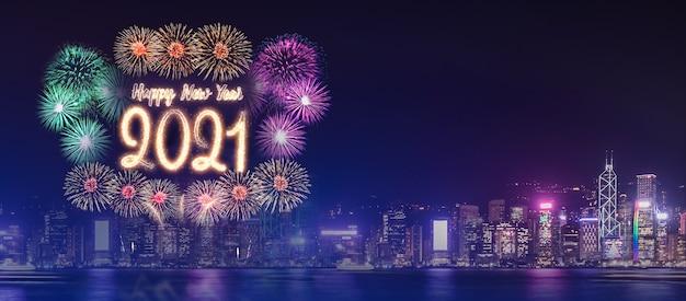 Feliz ano novo de 2021, fogos de artifício sobre a construção da cidade perto do mar durante a celebração noturna