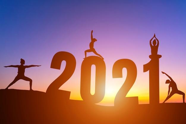 Feliz ano novo de 2021. mulher em silhueta praticando ioga de manhã cedo ao nascer do sol no horizonte.