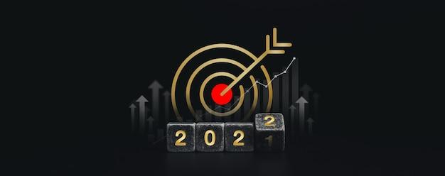 Feliz ano novo de 2022 e banner de conceito de sucesso com o símbolo do ícone de alvo grande objetivo dourado nos números de ouro 2022 em blocos de dados pretos lançando com setas de revolta em fundo escuro, estilo minimalista.