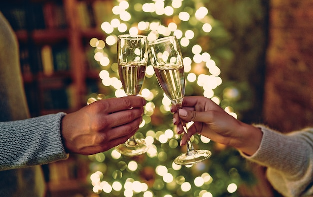 Feliz ano novo e feliz natal! copos com champanhe nas mãos com parabéns. árvore de natal com guirlandas no fundo.