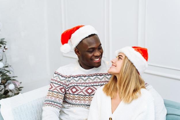 Feliz ano novo e feliz natal em casa juntos. sorrindo, jovem afro-americano e uma senhora caucasiana com chapéus de papai noel, abraçar e olhar para a câmera no interior da sala de estar com árvore e guirlandas.