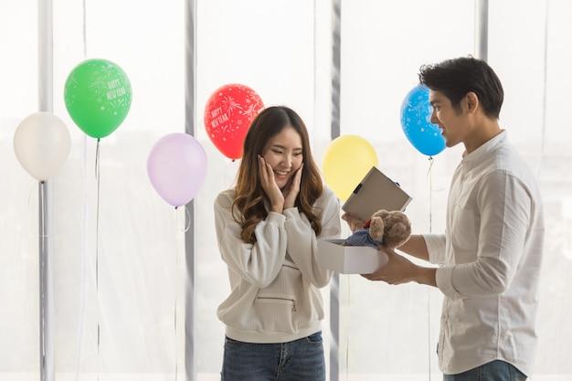 Feliz ano novo e o conceito de casal. retrato de mulher jovem asiática sorrindo e surpreso com uma boneca de urso em uma caixa de presente de homem com balão colorido