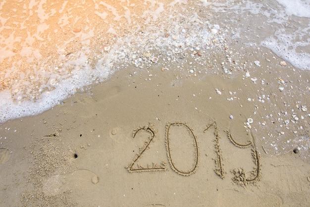 Feliz ano novo em fundo de areia