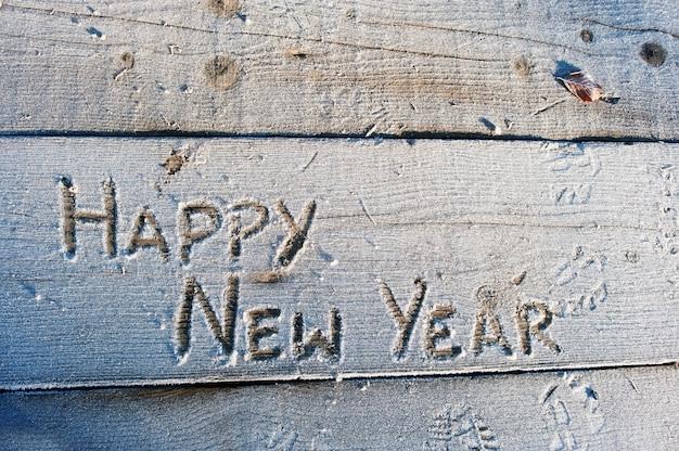 Feliz ano novo, escrito em uma flor de madeira com geadas