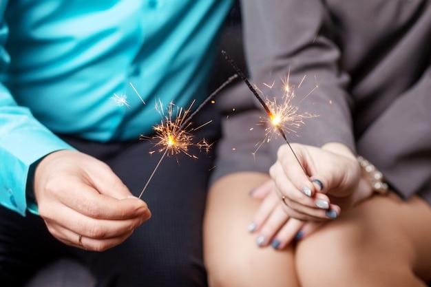 Feliz ano novo. estrelinhas brilhantes nas mãos do casal, família comemorando. fogos de artifício queimando nas mãos. boas festas