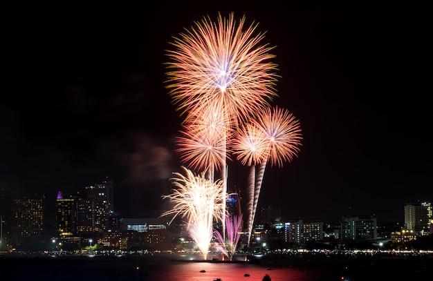 Feliz ano novo fogos de artifício sobre a paisagem urbana à noite. festival de celebração do feriado