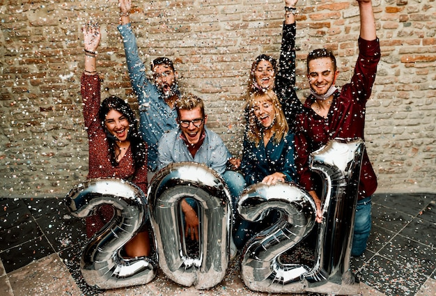 Feliz ano novo! grupo de jovens usando máscara facial comemorando 2021 Foto Premium
